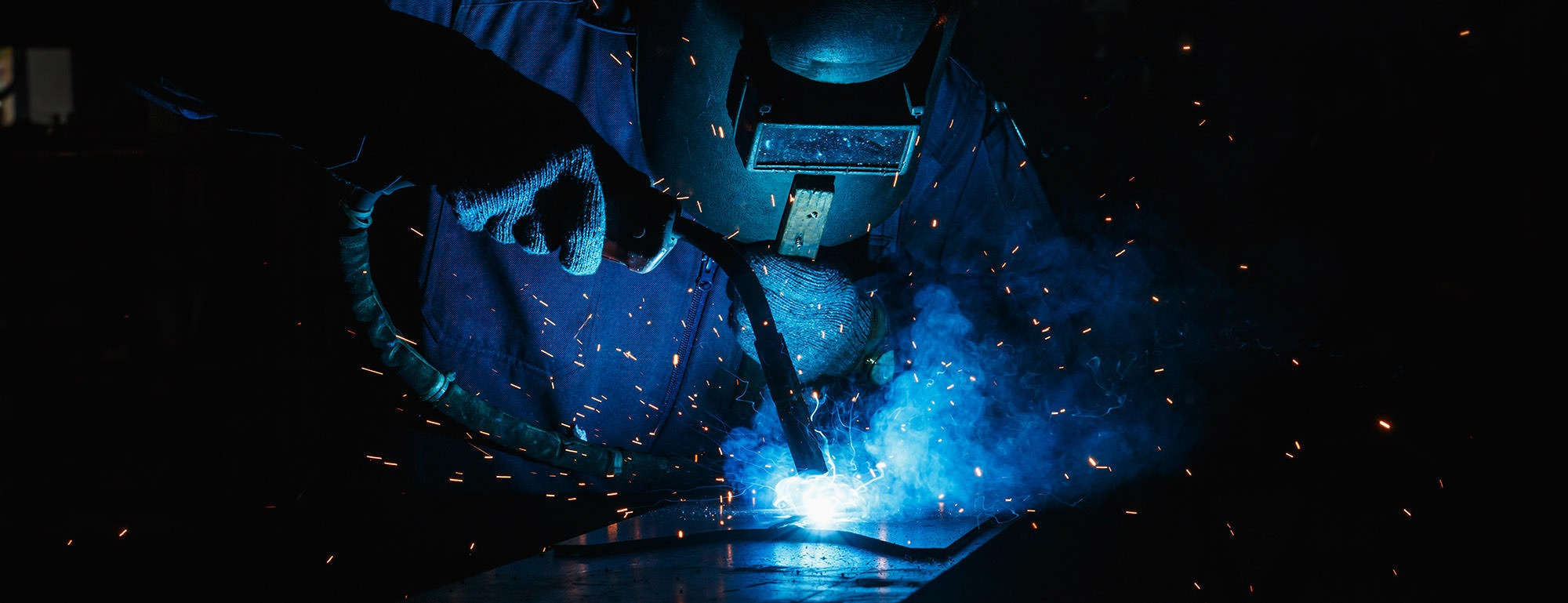 Welder of Metal Welding with sparks in industry steel weld  Sport e lavoro insieme per avviare Corsi di Formazione professionalizzanti welder of metal welding with sparks in industry steel weld